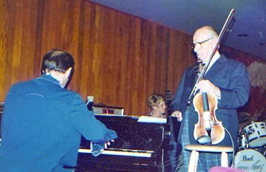Der Geiger Joe Venuti neben dem Klavier
