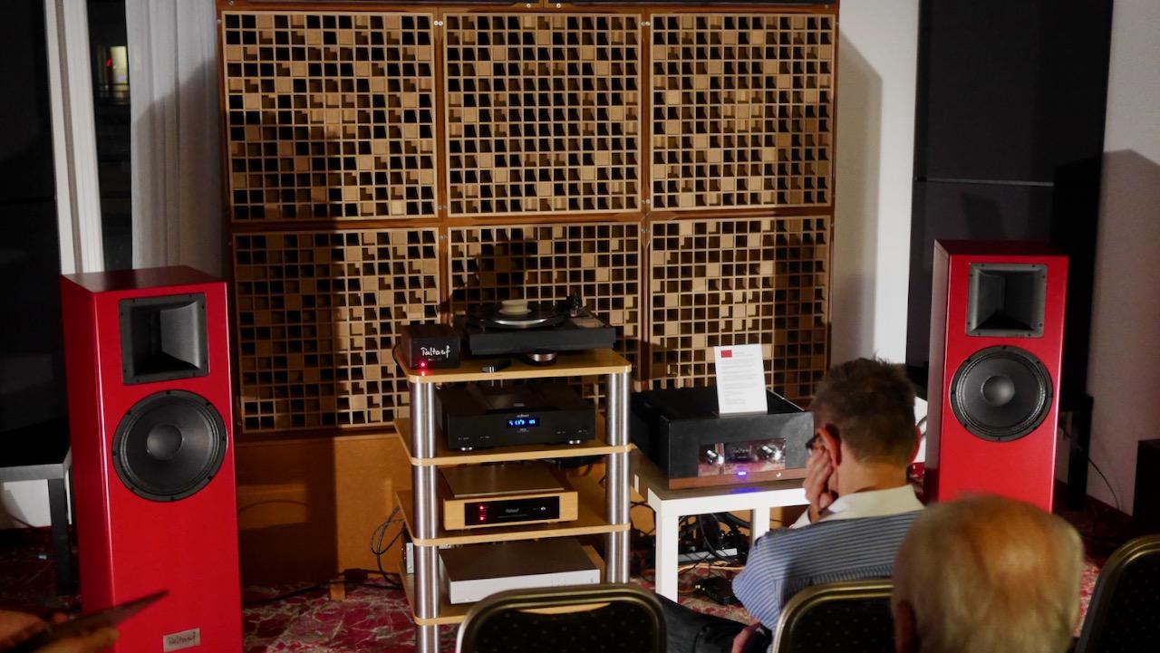 Zwei knallrote Lautsprecher vor Akustikwand.